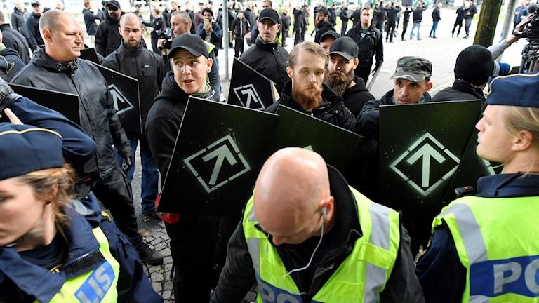 Medlemmar ur Nordiska Motståndsrörelsen och poliser.