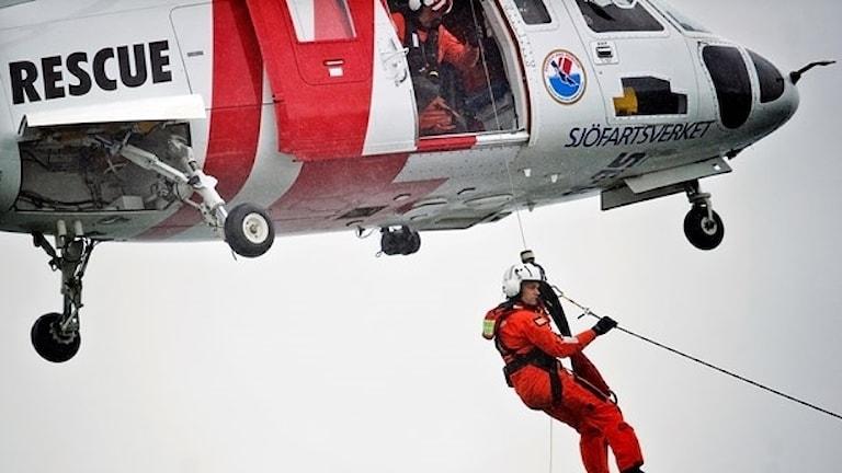 Räddningshelikopter med räddningspersonal som firar sig ned.
