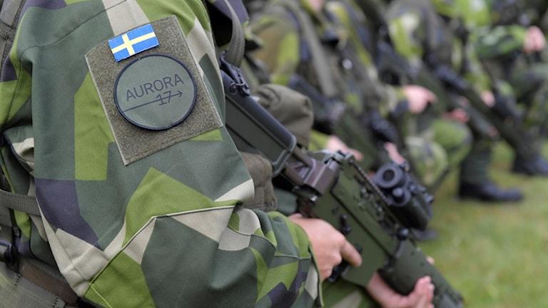 En soldat som håller i ett vapen och i bakgrunden ser man fler soldater.