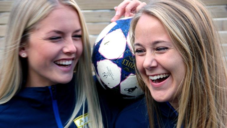 Maja Ericsson och Ellinor Månsson som skrattar och håller en fotboll mellan sig.