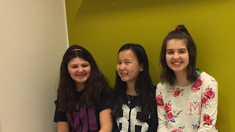 Tre flickor i klass 6B på Östra Torpskolan sitter på rad framför en grön och vit vägg