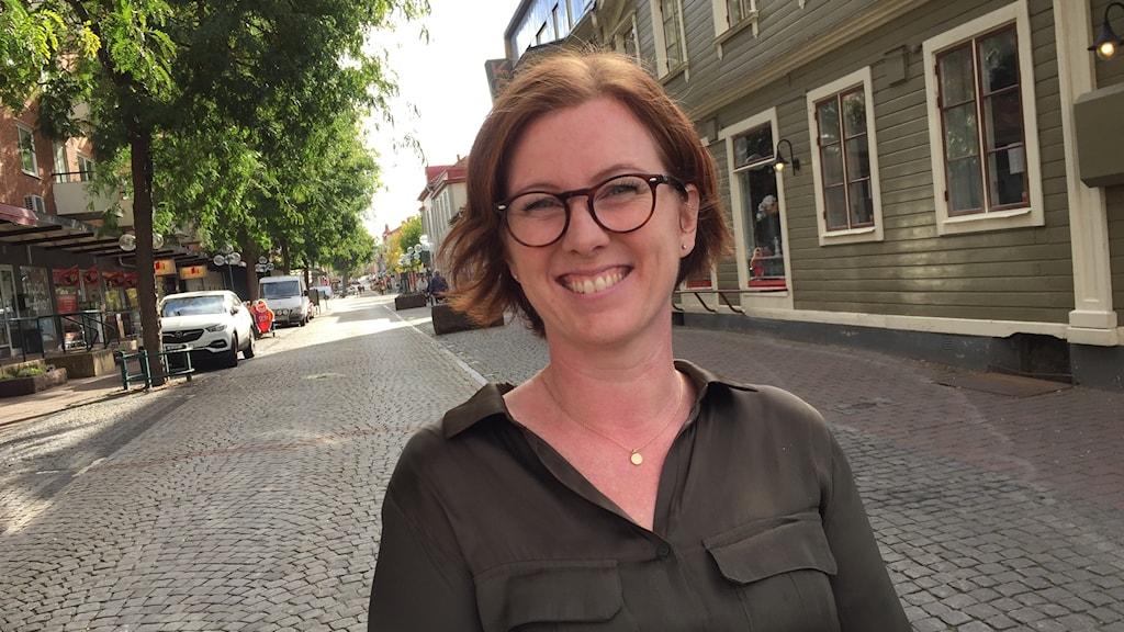 Anna Hultén står på en gata i Ronneby med träd på ena sidan och hus på andra.