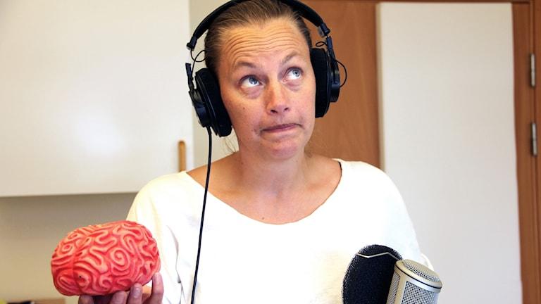 Programledaren Anette Eriksson står med en plasthjärna i ena handen och ser konfunderad ut.