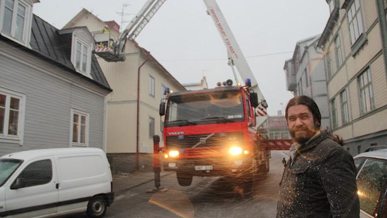 Peter Isaksson framför huset där räddningstjänsten håller på att jobba med att få fast taket.