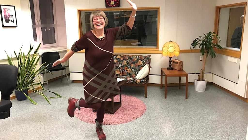 En kvinna i klänning står och balanserar på ett ben. Hon är glad.