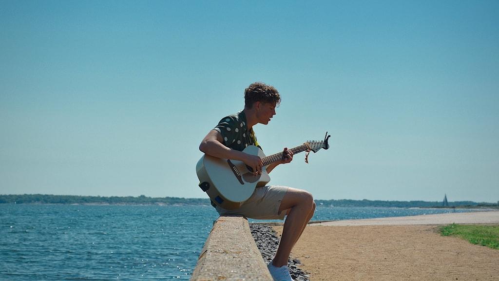 Linus med en gitarr vid en brygga en varm sommardag, havet i bakgrunden
