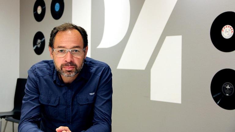Peppe Alfiero, kanalchef på P4 Blekinge, sitter vid ett bord med P4-loggan bakom sig.