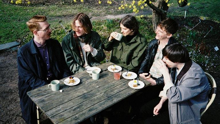 Bandet silverkulten runt ett bord i en trädgård.