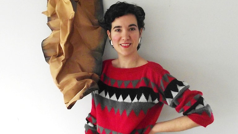 Kvinna i röd tröja bredvid ett brunt konstverk