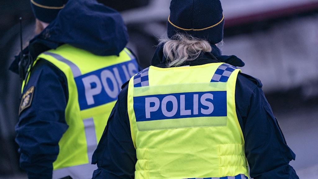 Två poliser med västar vända mot kameran