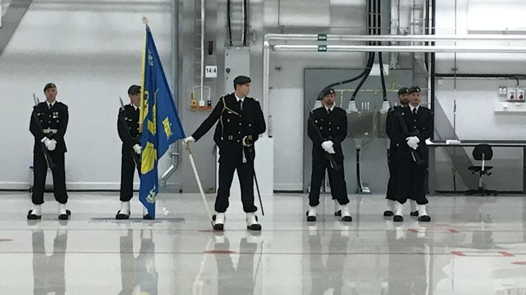 Fem mililtärer på rad i F17:s nya hangar.