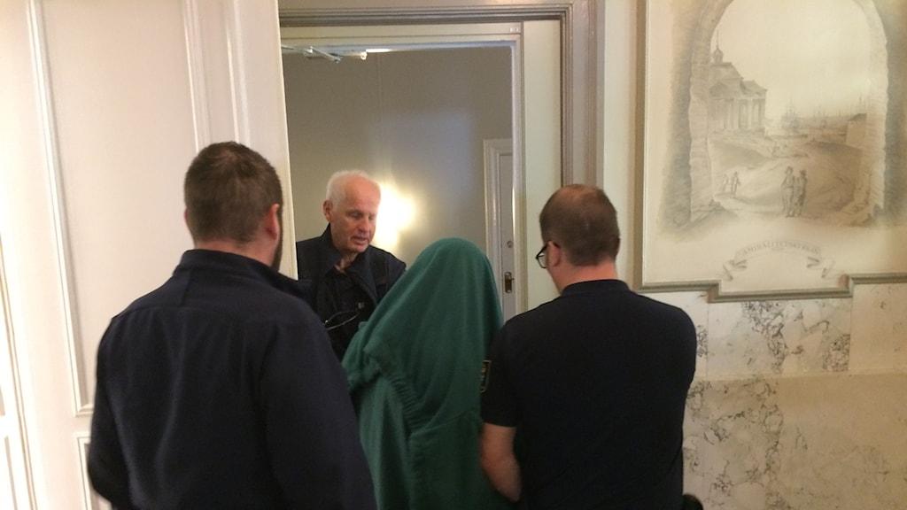 En åtalade mannen förs ut ur rättssalen med en grön tröja över huvudet.