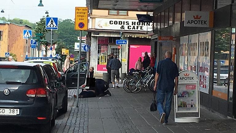 Två polisen sitter med en snattare på gatan.