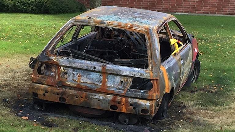 En helt utbränd bil på en gräsmatta.