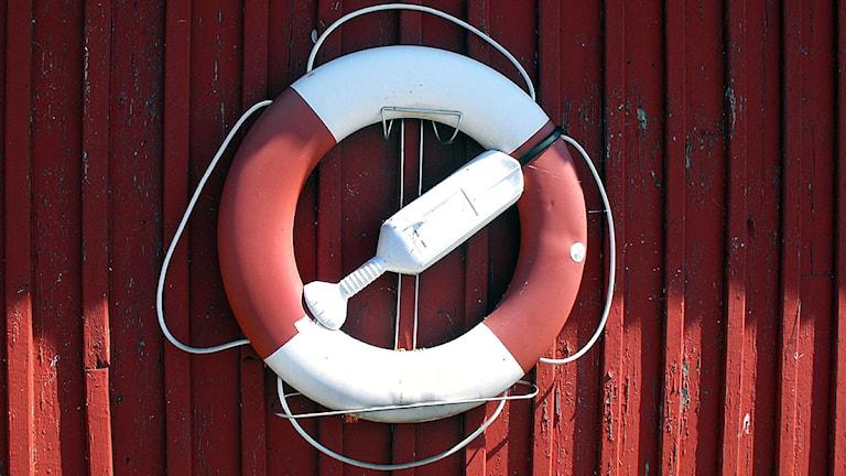 En livboj som hänger på en rödmålad vägg. Foto: Sigrid Ingesson/SR.