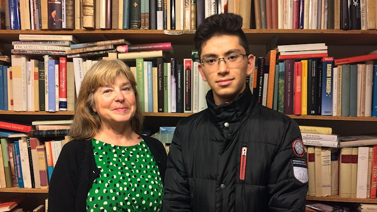 En kvinna och en kille står framför en bokhylla.