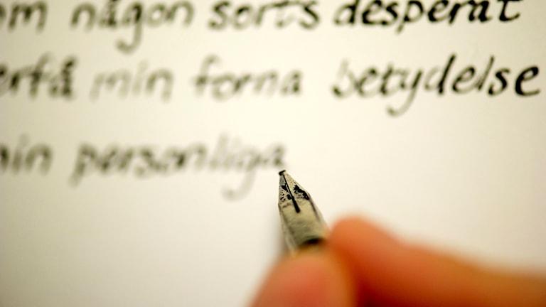 Någon skriver med bläckpenna