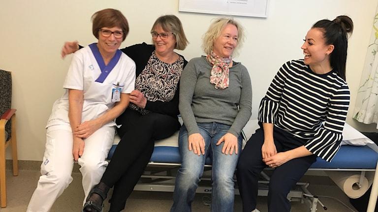 Fyra kvinnor sitter bredvid varandra på en brits.