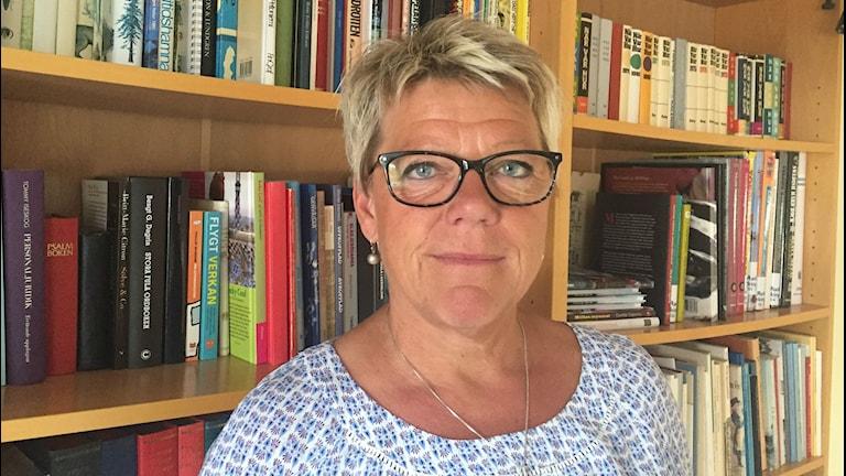 Porträttbild av Ann-Sofie Ström framför en bokhylla.