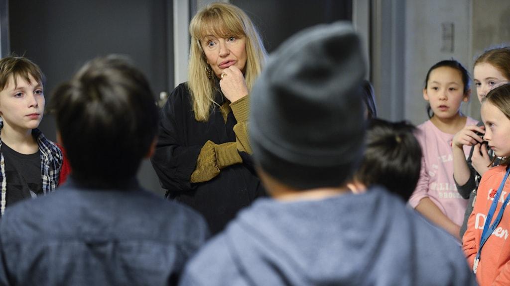 Lärare talar allvar med en grupp elever i skolkorridoren.
