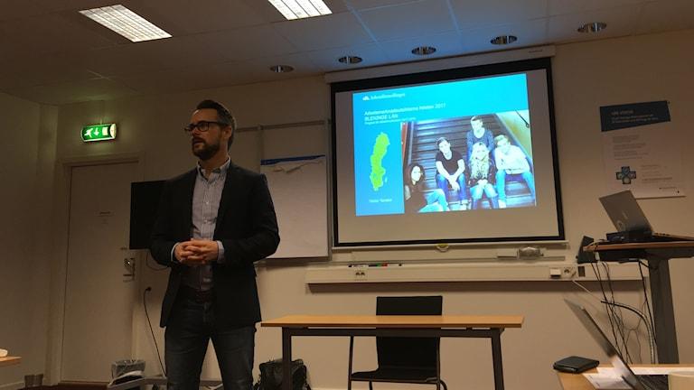 David i ett konferensrum med en powerpoint bakom sig. Han har kavaj och knäppta händer, ser åt vänster.