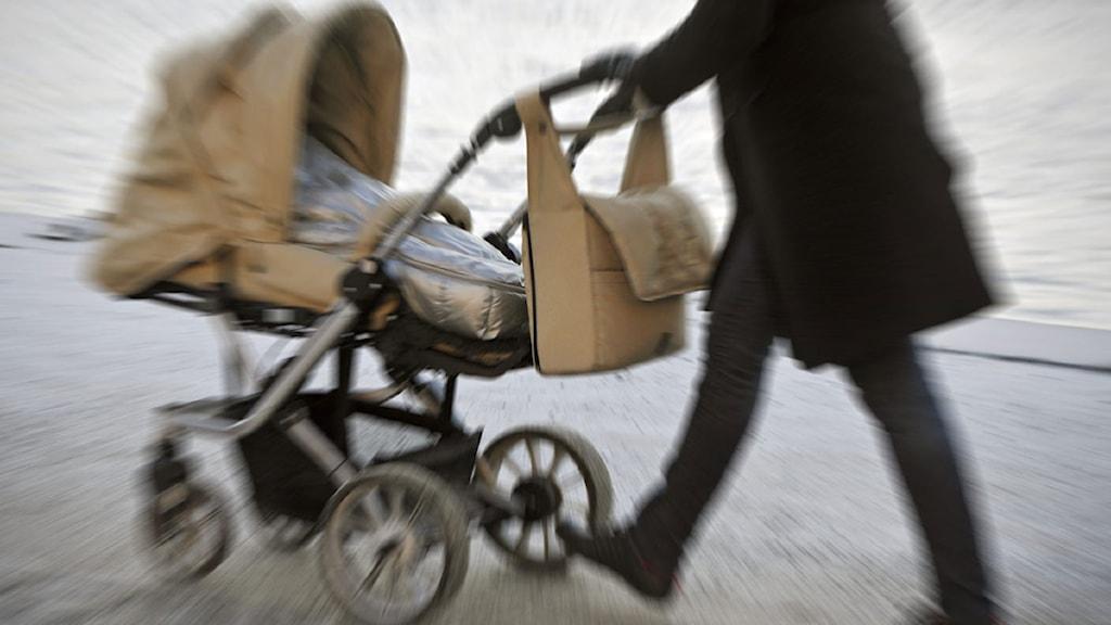 En person som kör en barnvagn.