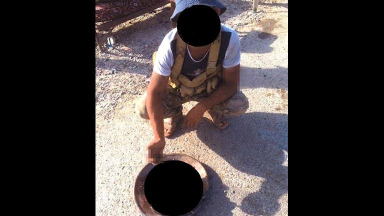 En man med maskerat ansikte sitter på huk framför en skål med maskerat innehåll.