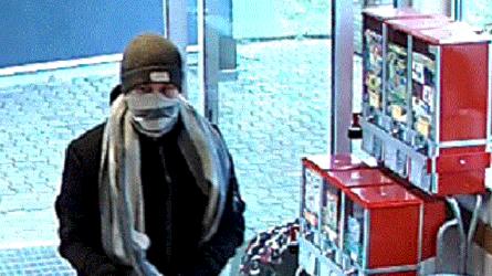 En maskerad man kommer in i en butiksentré, han har en halsduk runt ansiktet och en mössa på sig.