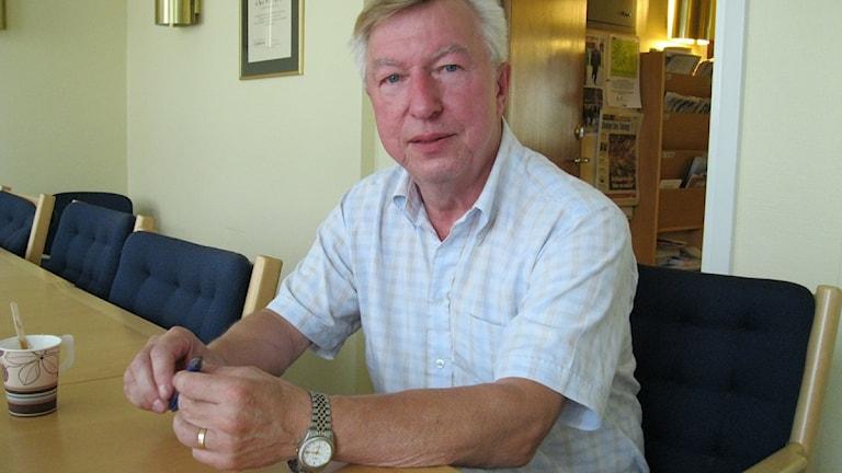 Kent Lewén, man i ljus skjorta sitter vid ett bord med en kaffekopp. Foto: Liselotte Olsson/ SR