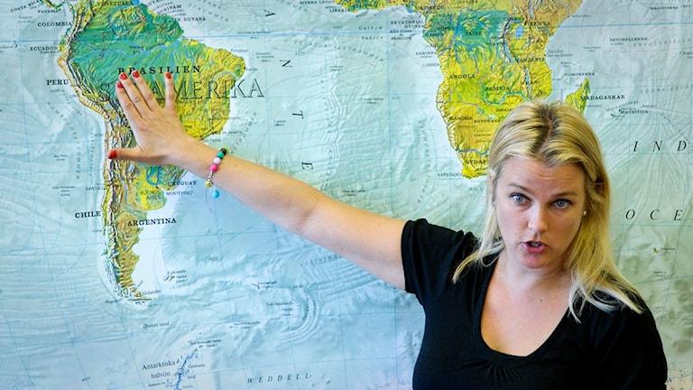 En kvinnlig lärare står och pekar på en stor världskarta, hon håller handen över Sydamerika. Foto: Janerik Henriksson/Scanpix.