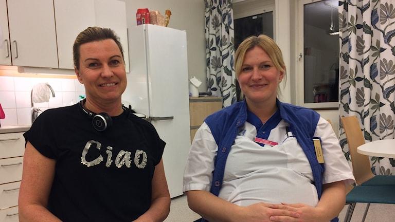 """Johanna Granberg i svart t-shirt med texten """"Ciao"""" i silverbokstäver. Hon har uppsatt hår och ett trådlöst headset runt halsen. Bredvid sitter Linnea Svensson i vita sjukvårdarekläder med blå väst och namnskylt. De sitter i ett lunchrum, bakom syns diskbänk och kylskåp."""