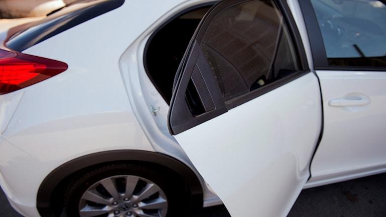 Bakdörren på en vit bil är öppen.