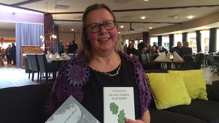 En glad kvinna som håller upp två böcker.