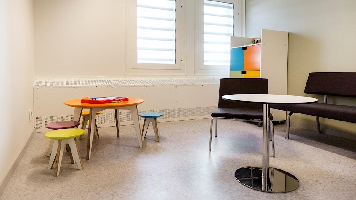 En liten lekhörna med färgglada pallar och ett bord i en häkteslokal.