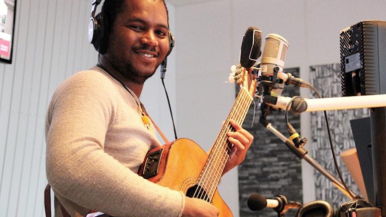 musikern Mpho Ludidi med en gitarr i handen.