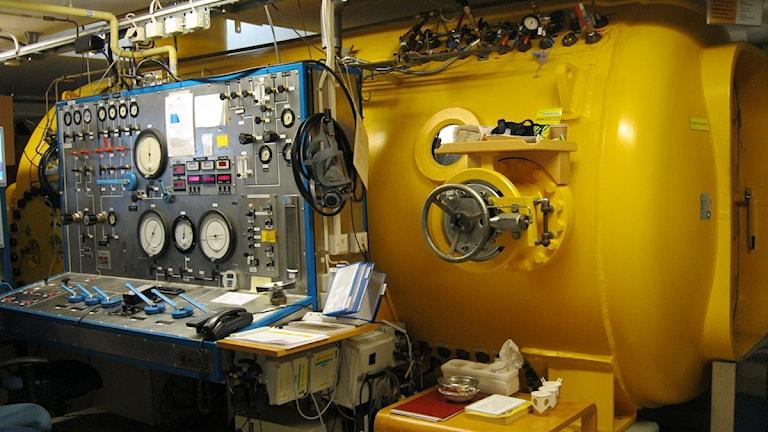 Gul stålcylinder och metallbord med visare. Foto:Carina Melin/Sveriges Radio.