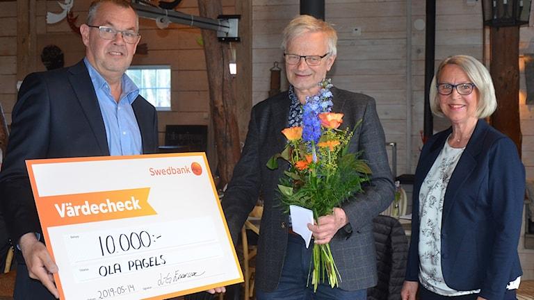 Blekinge Postens vd och chefredaktör Lars-Göran Enarsson överlämnar priset till Ola Pagels tillsammans Eleonor Elmstedt Ohlsson. Foto: Lars Sjösten