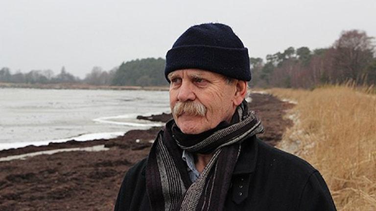 Ebbe Södergren står vid en strand, med mössa och halsduk. Foto: Josefin Lundén/Sveriges Radio.