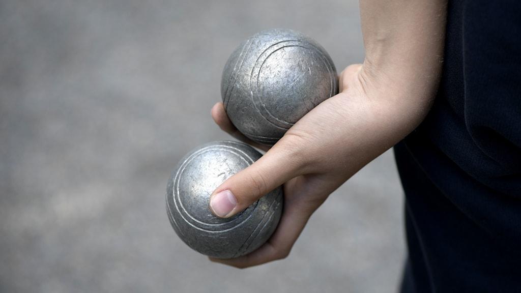 En hand som håller i två boulebollar.