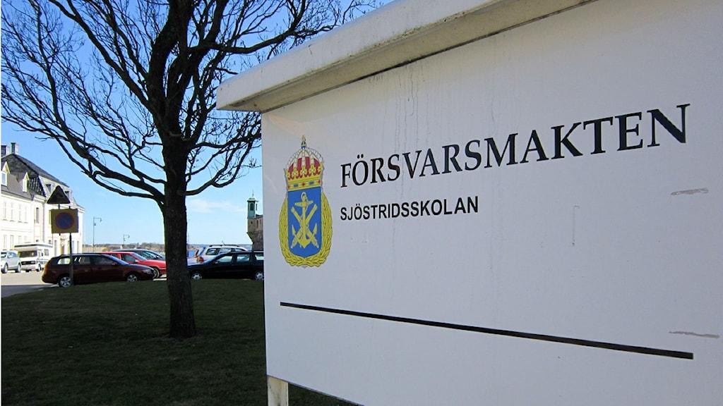Försvarsmakten Sjöstridsskolans skylt med en blå himmel och havet i bakgrunden. Foto: Jerker Hagman/Sveriges Radio.