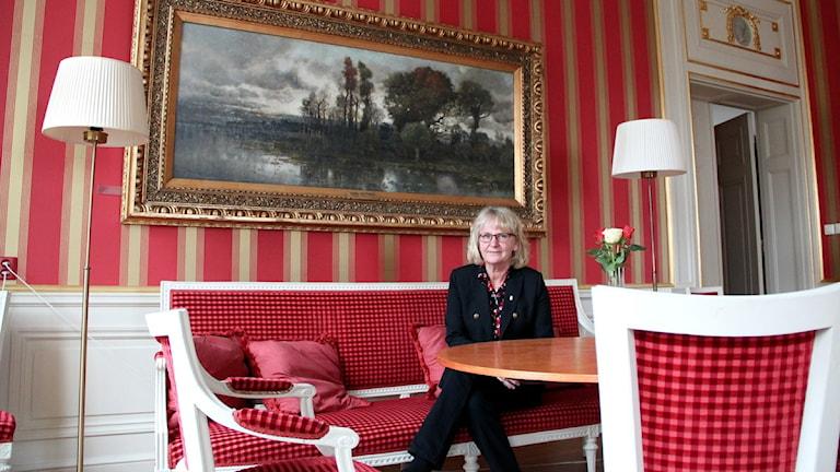 """Blekinges landshövding Berit Andnor Bylund sitter i en soffa i det """"röda rummet"""" på residenset i Karlskrona. Foto: Frank Luthardt/Sveriges Radio."""