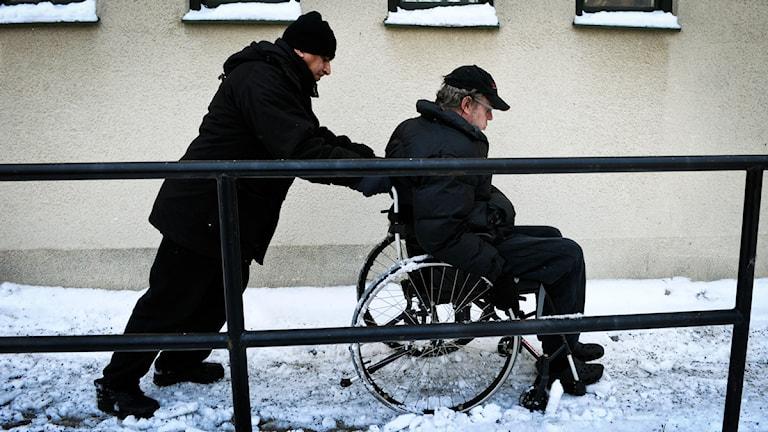 En man knuffar en rullstolsburen man på en snöig gata.