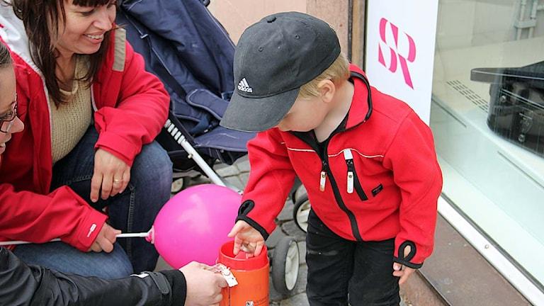 Ett barn skänker några välkomna slantar till Världens barn. Foto:Daniel Kjellander/Sveriges Radio.
