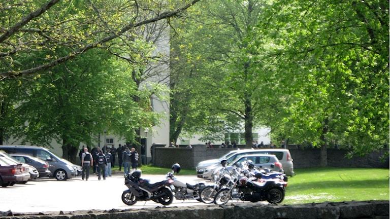 Motorcyklar och bilar på parkeringen och deltagare på väg till begravning. Foto: Jerker Hagman/Sveriges Radio.