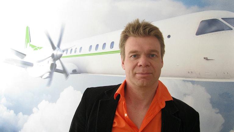 Jens arrysson, vd för Blekingeflyg. På väggen bakom Jens syns ett av bolagets flygplan. Foto: Mikael Eriksson/Sveriges Radio.