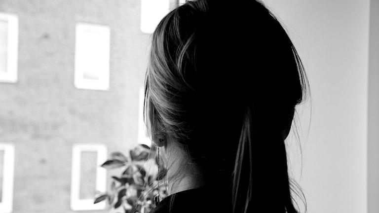 En kvinna sedd bakifrån och anonym. Bilden är svartvit.
