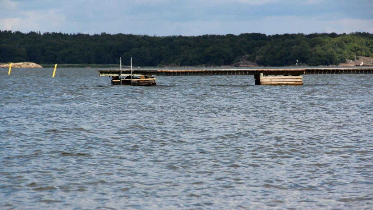 havet sett från stranden, folktomt, en brygga går ut från höger i bild