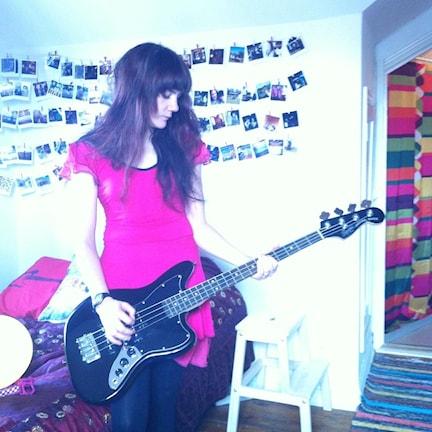 Lisa Bouvier står upp och spelar gitarr.