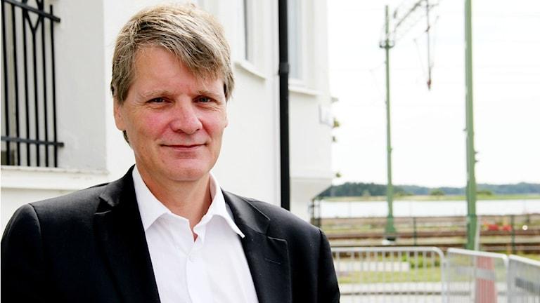 advokat Björn Attnarsson står framför sitt hem och kontor i Sölvesborg. I bakgrunden syns tågspåren.