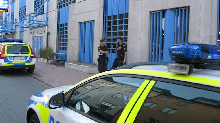 Två poliser står mellan två polisbilar. Foto: Jerker Hagman/Sveriges Radio.